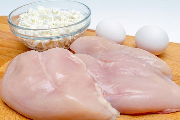 Ruwe kippenborst, graangewassen, eieren, kwark dichte omhooggaand op houten achtergrond eiwit gezond dieet