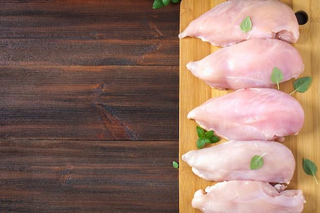 Ruwe kippenfilets op een scherpe raad tegen de achtergrond van een houten lijst.