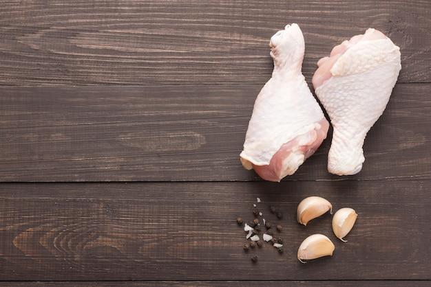Ruwe kippentrommelstokken en peper, zout, knoflook op houten achtergrond