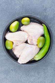 Ruwe kippenvleugels en spaanse peperpeper op zwarte plaat.