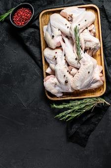 Ruwe kippenvleugels in een houten kom. boeren biologisch vlees. bovenaanzicht