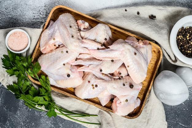 Ruwe kippenvleugels in een houten kom. bovenaanzicht