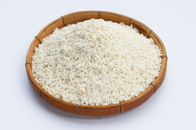 Ruwe kleverige rijst in bamboemand op witte achtergrond.
