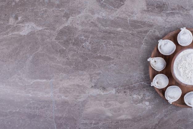Ruwe knoedels op een houten bord.
