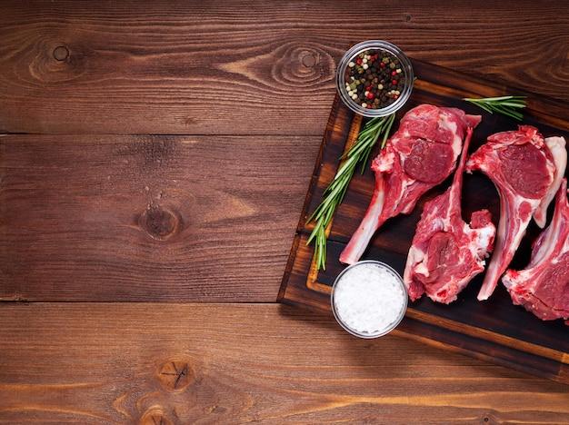 Ruwe lamskoteletten op been op donkere bruine houten achtergrond, lamsribben