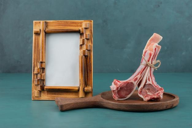 Ruwe lamskoteletten op een houten bord met omlijsting.