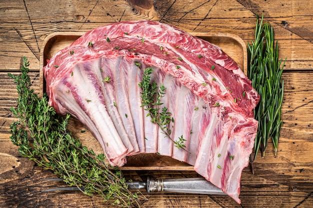Ruwe lamsrack ribben op de snijplank van de slager met kruiden