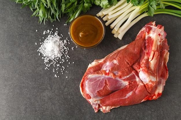 Ruwe lamsvlees met kruiden op houten bord over oude houten oppervlak. close-up, selectieve aandacht.