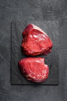 Ruwe lapjes vleesfilet mignon die op het koken wordt voorbereid. ossenhaas. zwarte achtergrond. bovenaanzicht