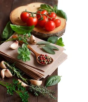 Ruwe lasagne pasta, groenten en kruiden op een houten achtergrond