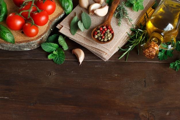 Ruwe lasagne pasta, groenten en kruiden op een houten tafel
