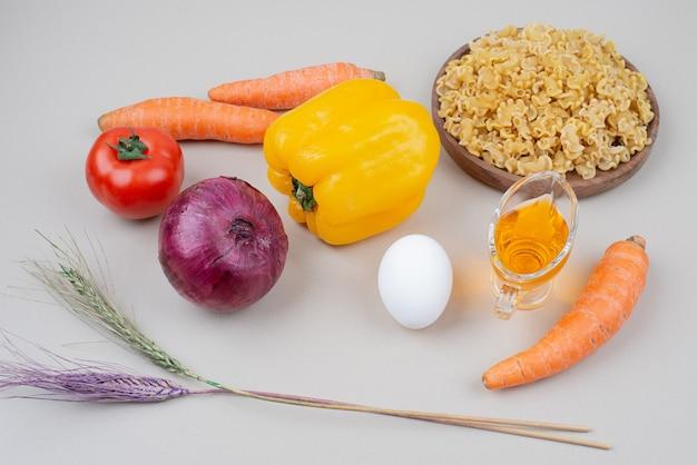 Ruwe macaroni met groenten en ei op witte ondergrond