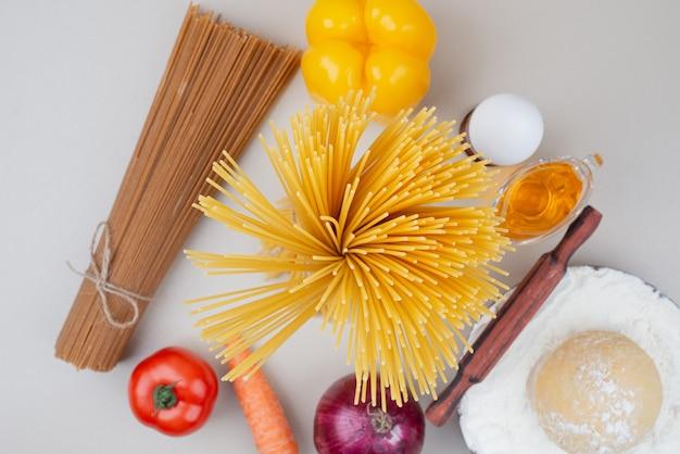 Ruwe macaroni met tomaat en ei op houten plaat