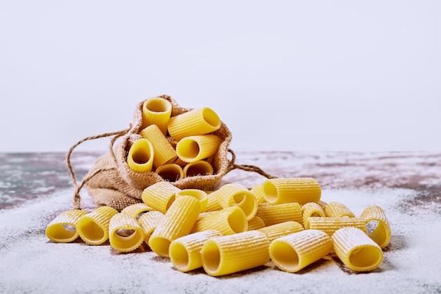 Ruwe macaroni op witte ondergrond.