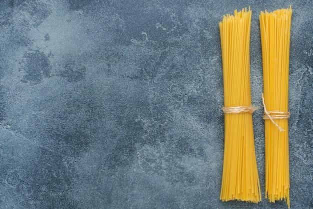 Ruwe macaroni, spaghetti op een donkere stenen tafel met kopie ruimte. zelfgemaakte italiaanse pasta.