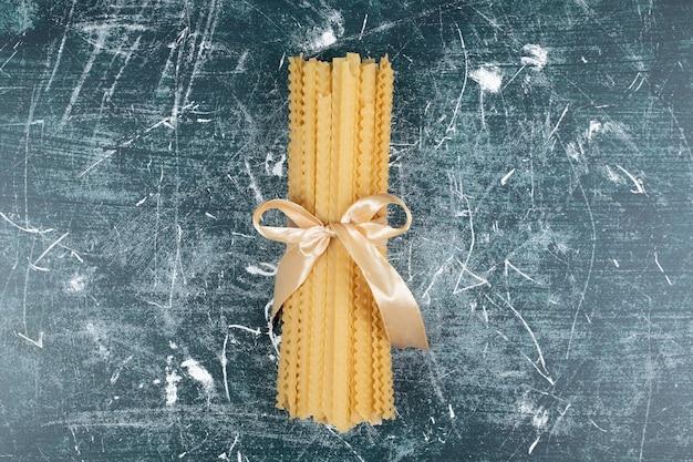 Ruwe mafaldine pasta gebonden met lint op blauwe tafel. hoge kwaliteit foto