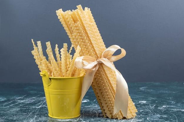 Ruwe mafaldine pasta in emmer en gebonden met lint. hoge kwaliteit foto