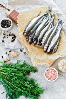 Ruwe makreel op een houten snijplank, dille, roze zout, peper en knoflook.
