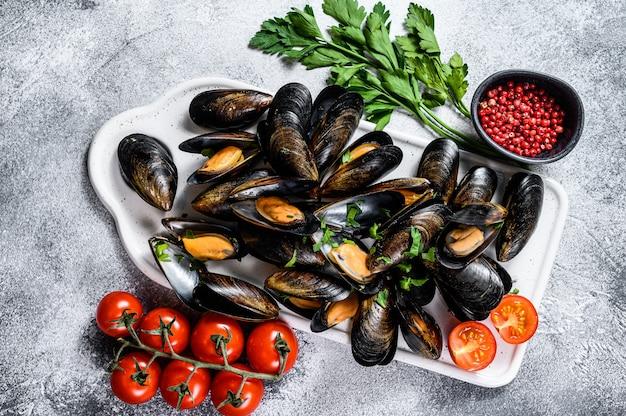 Ruwe mosselen in shells op een hakbord. het concept het koken van zeevruchten in tomatensaus met peterselie.