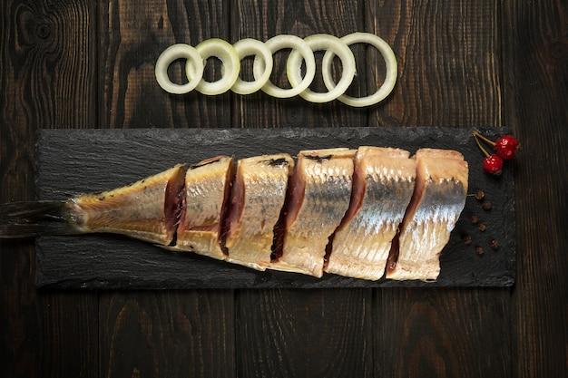 Ruwe noorse haring met uien en kruiden op een dienende raadsclose-up.