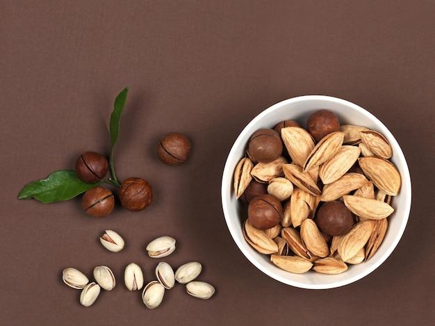 Ruwe noten in een houten kom macadamia en pistache op bruine suède achtergrond