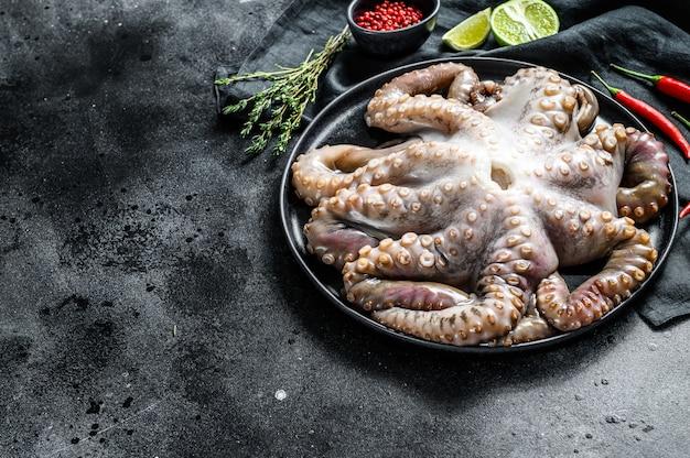 Ruwe octopus in een plaat met koken ingrediënten. zwart oppervlak. bovenaanzicht. kopieer ruimte