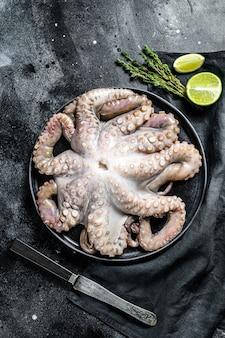 Ruwe octopus in een plaat met koken ingrediënten. zwart oppervlak. bovenaanzicht