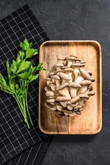 Ruwe oesterzwammen in een houten kom met peterselie. biologisch voedsel. zwarte achtergrond. bovenaanzicht. ruimte voor tekst