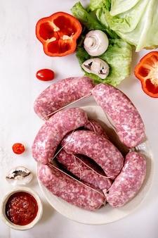 Ruwe ongekookte italiaanse worstsalsiccia in plaat op witte marmeren achtergrond. groene salade, groenten en tomatensaus rondom. plat leggen.