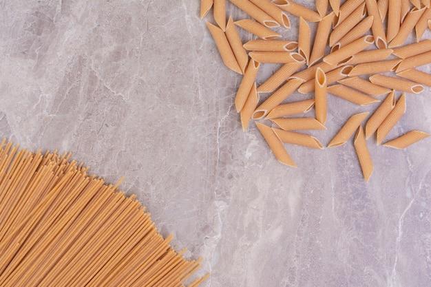 Ruwe ongekookte pasta's die op de grijze ruimte worden geïsoleerd.