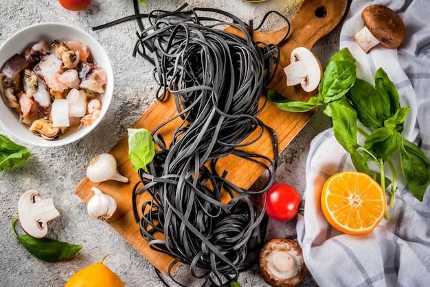 Ruwe ongekookte zwarte de spaghettideegwaren van de inktvisinkt met ingrediënten voor het koken