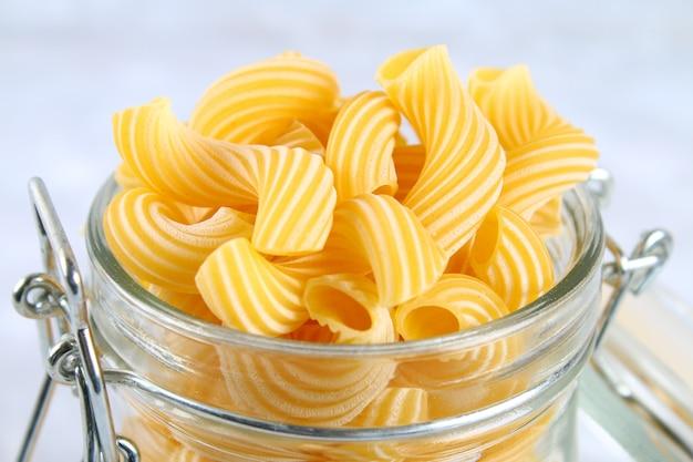 Ruwe pasta cavatappi of cellentani op een grijze tafel
