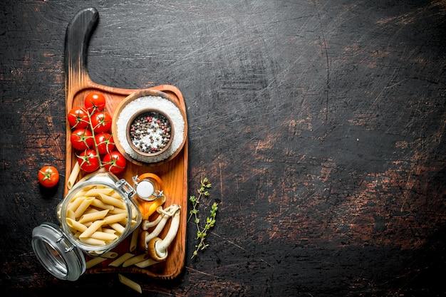 Ruwe pasta in een glazen pot met champignons, tomaten en olie in een fles.