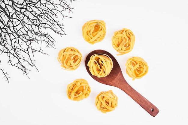 Ruwe pasta in een houten lepel, bovenaanzicht.