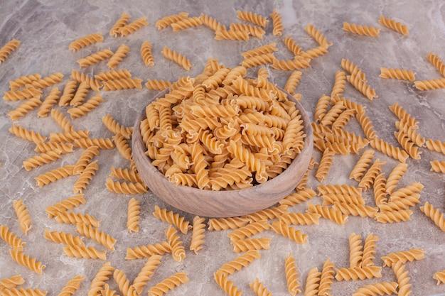 Ruwe pasta in een rustieke houten kop en op het grijze marmer.