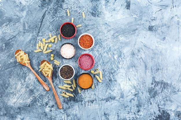 Ruwe pasta in houten lepels met kruiden bovenaanzicht op een grijze gips achtergrond