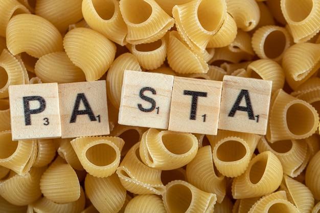 Ruwe pasta met houten letters.