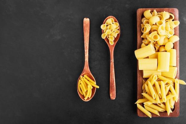 Ruwe pastasoorten op een houten schotel, bovenaanzicht.