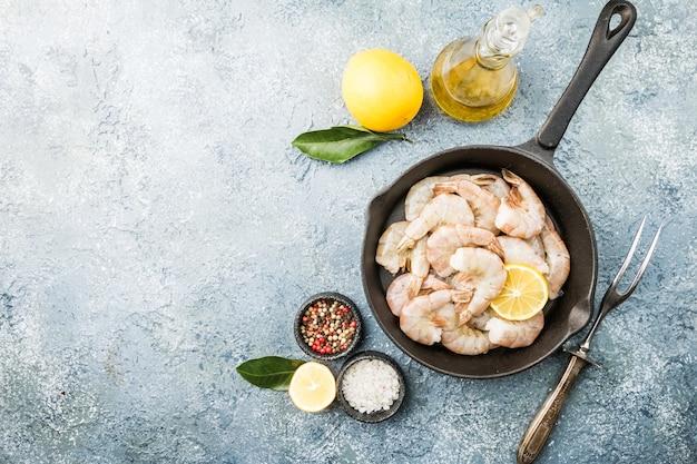 Ruwe reuzengarnalen met citroen en kruiden in een koekenpan over grijs