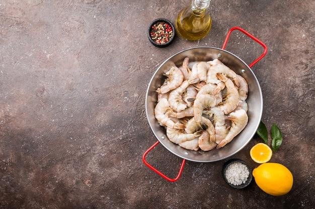 Ruwe reuzengarnalen met citroen en kruiden in een koekenpan