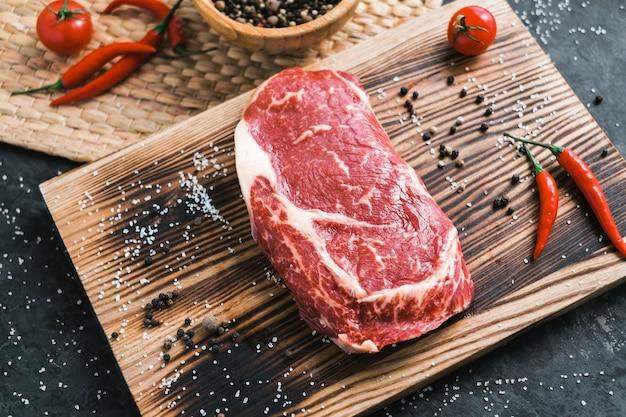 Ruwe rib eye biefstuk op een houten bord met chili peper, zout en rozemarijn