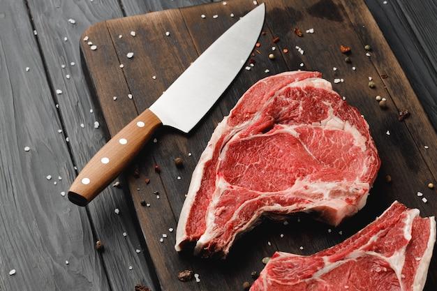 Ruwe rib eye steak op bruin houten bord