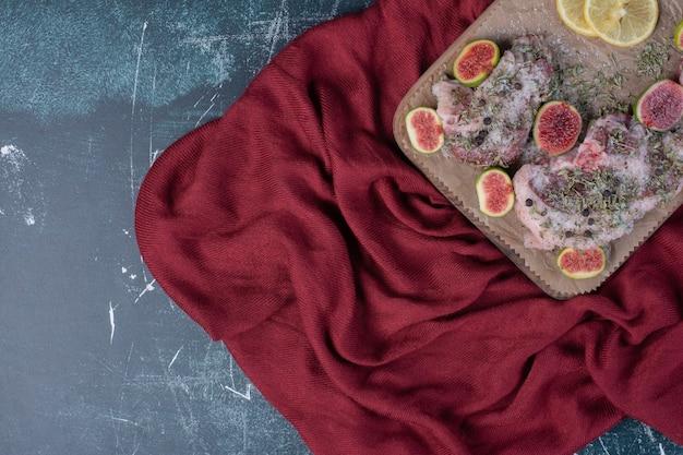 Ruwe ribben in een houten bord met vijgen, gedroogde kruiden en rode doek.