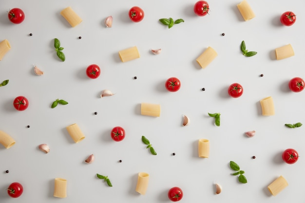 Ruwe rigatonideegwaren die van durumtarwemeel, rode rijpe tomaten en groene basilicum op witte achtergrond worden gemaakt. ingrediënten voor de italiaanse keuken. traditie keuken. nourishig pastagerecht en voedselconcept