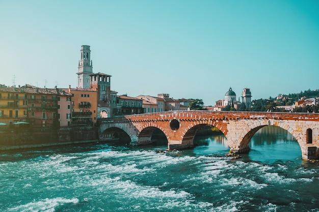 Ruwe rivierdijk, boogbrug, golven en oriëntatiepunten, historische gebouwen en zonnige dag in de oude stad verona, italië.