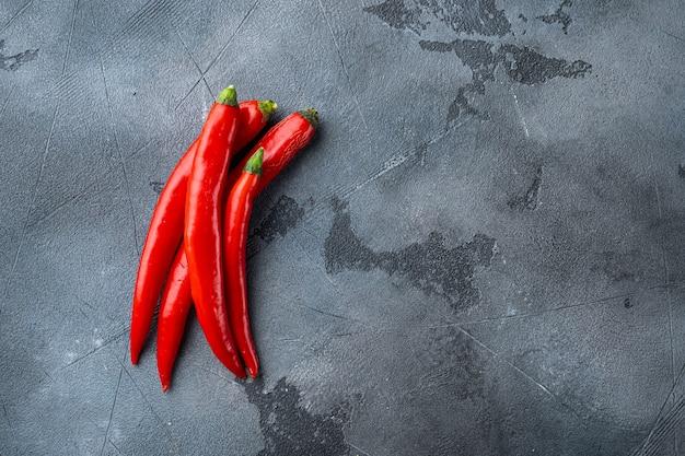 Ruwe rode chili peper set, op grijze achtergrond, bovenaanzicht met ruimte voor tekst