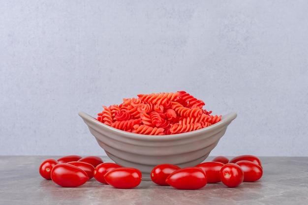 Ruwe rode fusilli pasta in een kom naast tomaten, op het marmeren oppervlak
