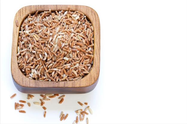 Ruwe rode rijst in een houten kop die op witte achtergrond wordt geïsoleerd.
