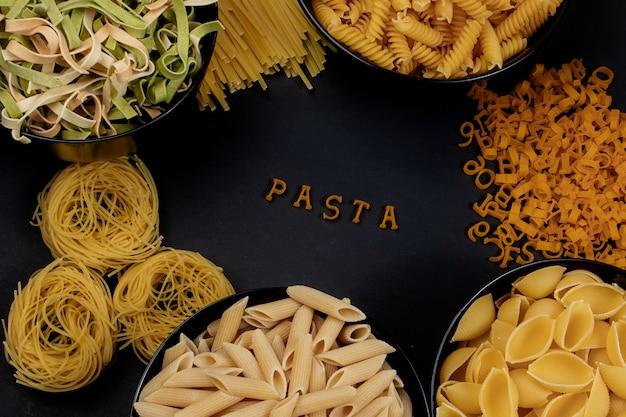 Ruwe ronde pasta op een donkere achtergrond. het woord pasta gemaakt van houten letters in het midden. het concept van heerlijk eten. bovenaanzicht, plat lag, kopieer ruimte.