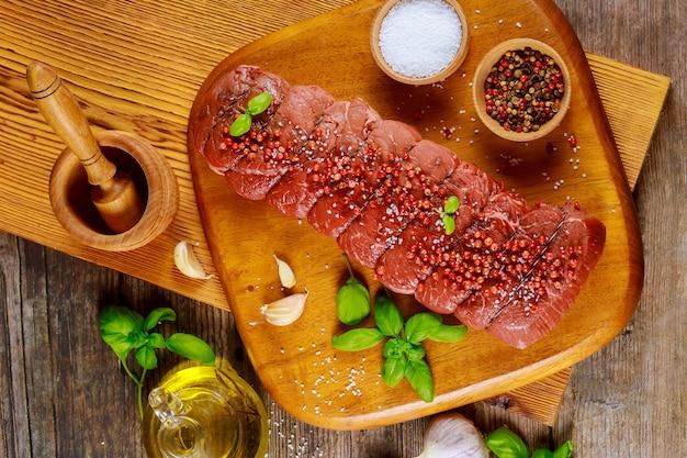 Ruwe rundvleeslapjes vlees met zwarte peperbollen en zout op houten raad. bovenaanzicht.